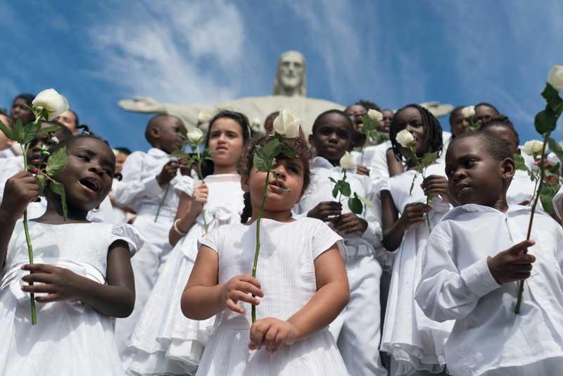 Crianças refugiadas cantam no Cristo Redentor para marcar o sexto aniversário da guerra síria (AP Photo/Renata Brito)