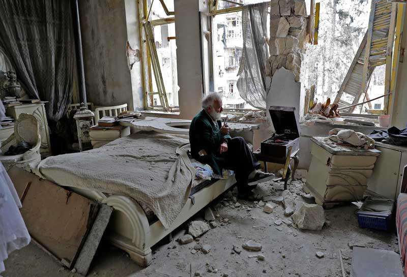 Mohammad Mohiedine Anis, de 70 anos, fuma cachimbo e ouve música no quarto destruído, em Aleppo. Seu sonho é consertar os carros destruídos pela guerra (JOSEPH EID/AFP)